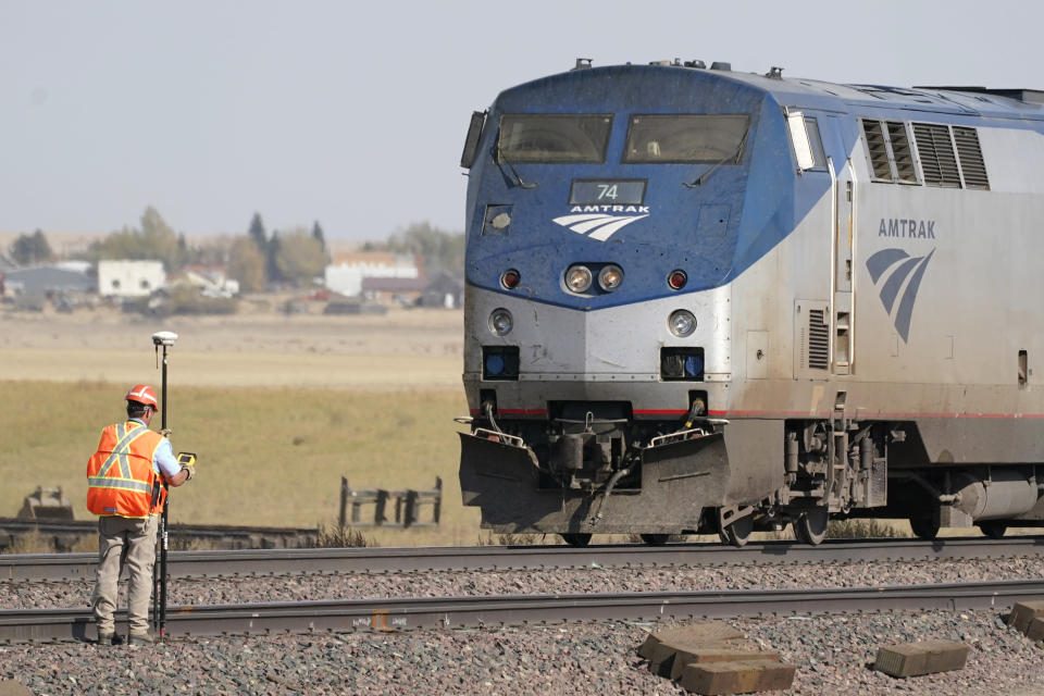 A person uses survey equipment, Sunday, Sept. 26, 2021, near an Amtrak train that derailed Saturday just west of Joplin, Mont. The westbound Empire Builder was en route to Seattle from Chicago, with two locomotives and 10 cars. (AP Photo/Ted S. Warren)