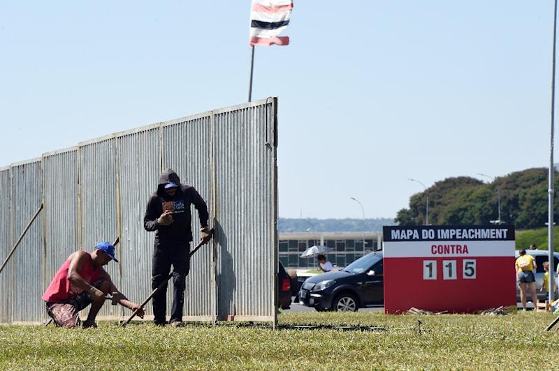 Workers set up a protective fence to separate the demonstrators against the impeachment of President Dilma Rousseff from those supporting it, in front of the Congress in the Esplanada dos Ministerios in Brasilia, on April 10, 2016