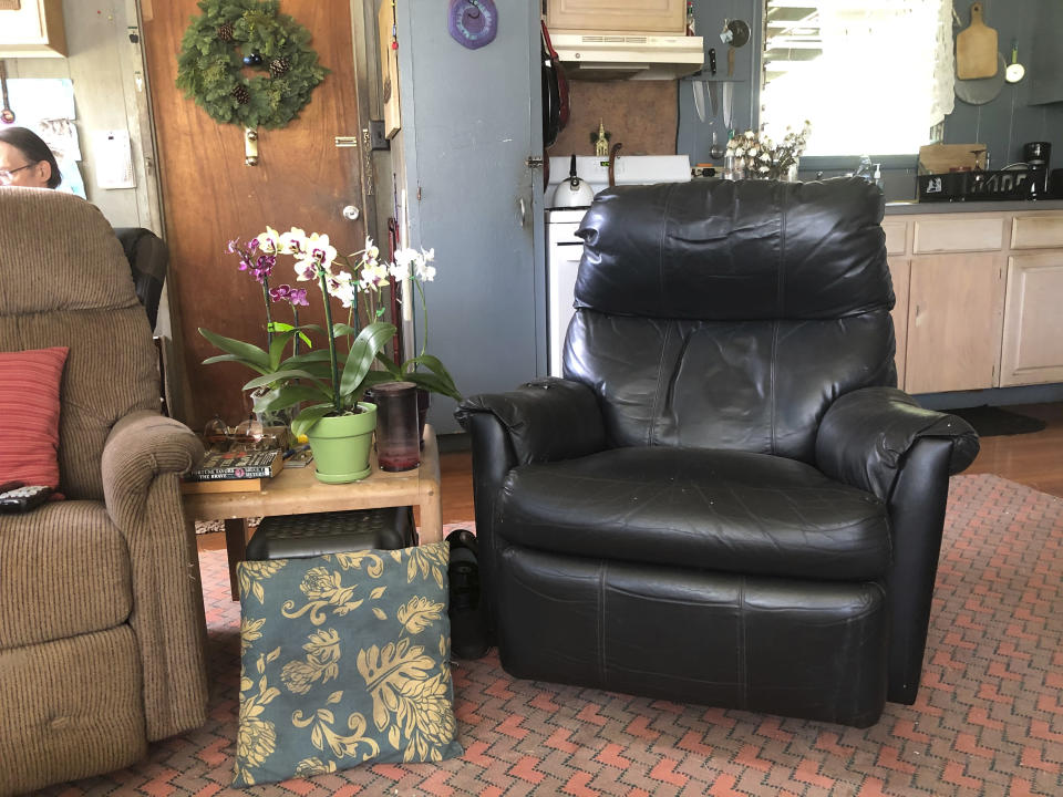In this Dec. 11, 2020 photo provided by Ron Clark's roommate Suzanne Williams, Clark's favorite chair, right, sits empty in their home in Kapaa, Hawaii after Clark died of COVID-19 on the island of Kauai in November. Early and aggressive local measures coupled with a strictly-enforced statewide travel quarantine kept Kauai's 72,000 residents mostly healthy — the island had only 61 known coronavirus cases from March through September. But on Oct. 15, the state launched a pre-travel testing program to reignite Hawaii's decimated tourism economy. Kauai went from having no infections in early October to at least 84 new cases in seven weeks. The surge seeded community transmission and led to the island's first — and so far only — COVID-19 death: Ron Clark, who worked for decades as a tour driver. (Suzanne Williams via AP)