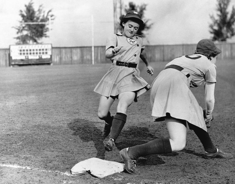 A woman of the All-American Girls Professional Baseball League steps on a base.