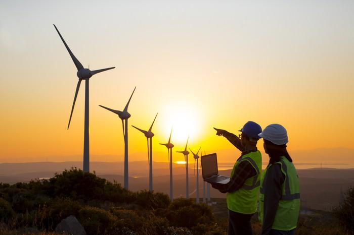 Two people wearing hard hats, with the man holding a laptop and pointing at a row of wind turbines during sunset.