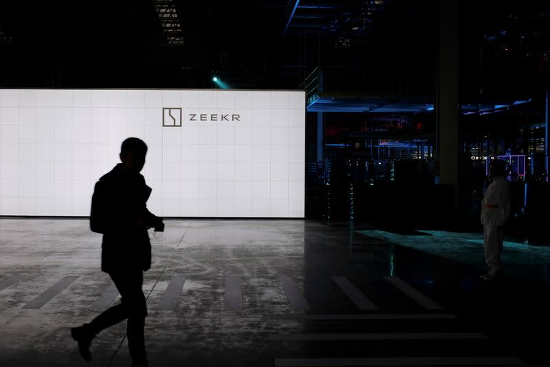 Man walks past a sign of Geely's new brand Zeekr at its factory in Ningbo