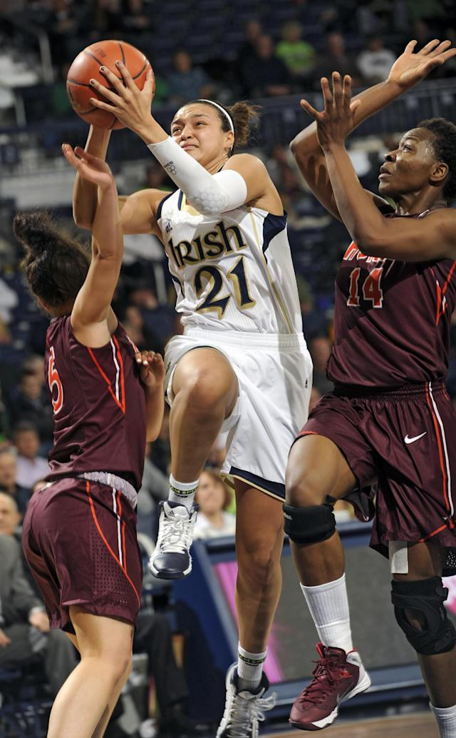 Notre Dame guard Kayla McBride (21) drives the lane between Virginia Tech forward Uju Ugoka, right, and guard Vanessa Panousis during the first half of an NCAA college basketball game, Thursday, Jan. 30, 2014 in South Bend, Ind. (AP Photo/Joe Raymond)