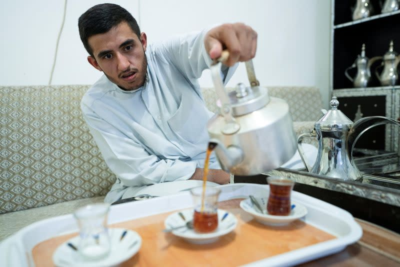 Ahmad al-Enezi, a stateless frontline worker pours tea at his home in Sulaibiya