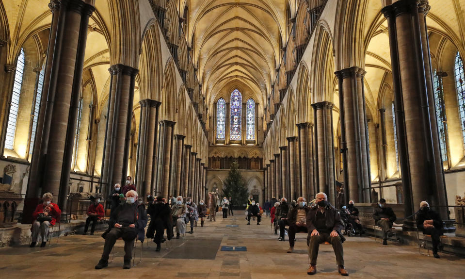 FILE - In this Wednesday, Jan. 20, 2021 file photo, people sit and wait after receiving their Pfizer-BioNTech vaccination at Salisbury Cathedral in Salisbury, England. Thanks to an efficient vaccine roll out program and high uptake rates, Britain is finally saying goodbye to months of tough lockdown restrictions. From Monday May 17, 2021, all restaurants and bars can fully reopen, as can hotels, cinemas, theatres and museums, and for the first time since March 2020, Britons can hug friends and family and meet up inside other people's houses. (AP Photo/Frank Augstein, File)
