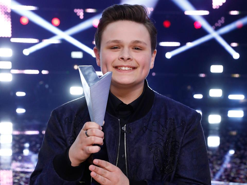 """Carter Rubin holding his trophy from winning """"The Voice"""""""