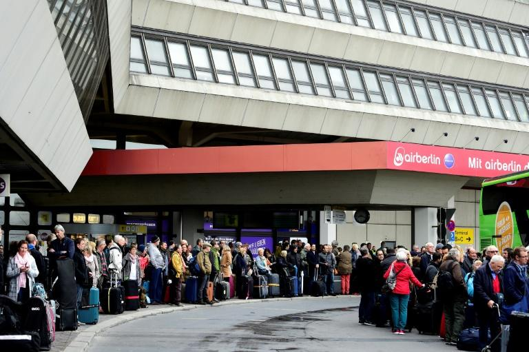 Passengers queue for bus transport during a wage strike by ground staff at Berlin's Tegel airport on March 10, 2017