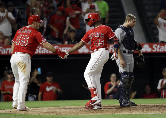 Los Angeles Angels' Justin Upton, center, is met at home plate by teammate Mike Trout, left, after Upton's two-run home run against the Seattle Mariners during the seventh inning of a baseball game Friday, July 12, 2019, in Anaheim, Calif. (AP Photo/Marcio Jose Sanchez)