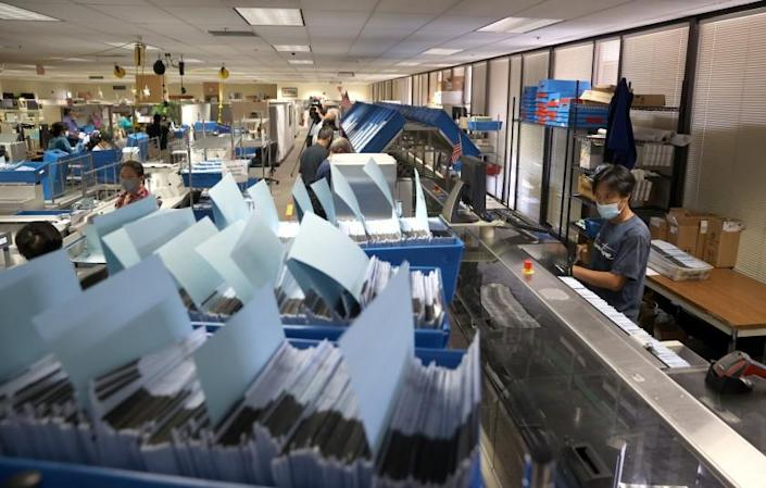 SAN JOSE, CALIFORNIA - AUGUST 25: A worker runs mail-in-ballots through a sorting machine at the Santa Clara County registrar of voters office on August 25, 2021 in San Jose, California. The Santa Clara County registrar of voters is preparing to take in and process thousands of ballots in the recall election of Gov. Gavin Newsom as early voting is underway in the state of California. (Photo by Justin Sullivan/Getty Images)