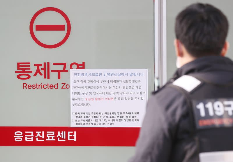 A rescue worker walks past a notice about new coronavirus that has broken out in China, at a hospital where a Chinese woman who flew from Wuhan, China, and has been confirmed its first case of a new coronavirus, is isolated, in Incheon