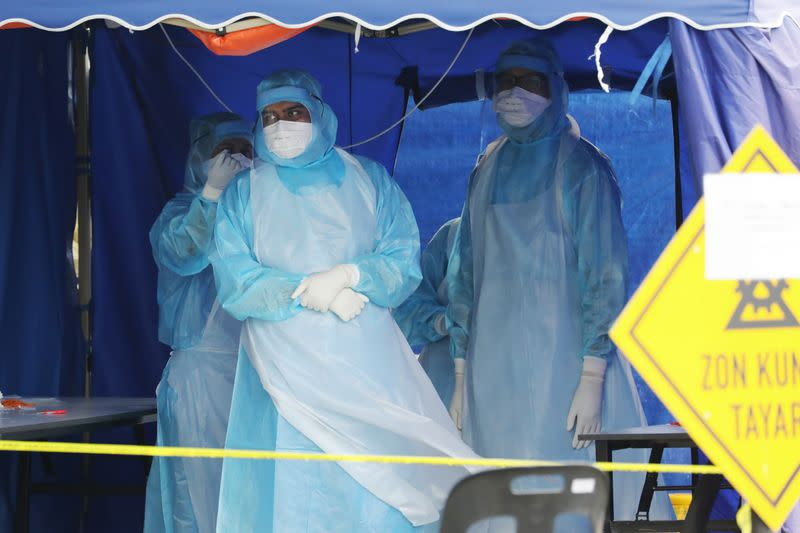 Health workers in protective suits wait for patients in a tent erected to test for coronavirus at a clinic, in Kuala Lumpur