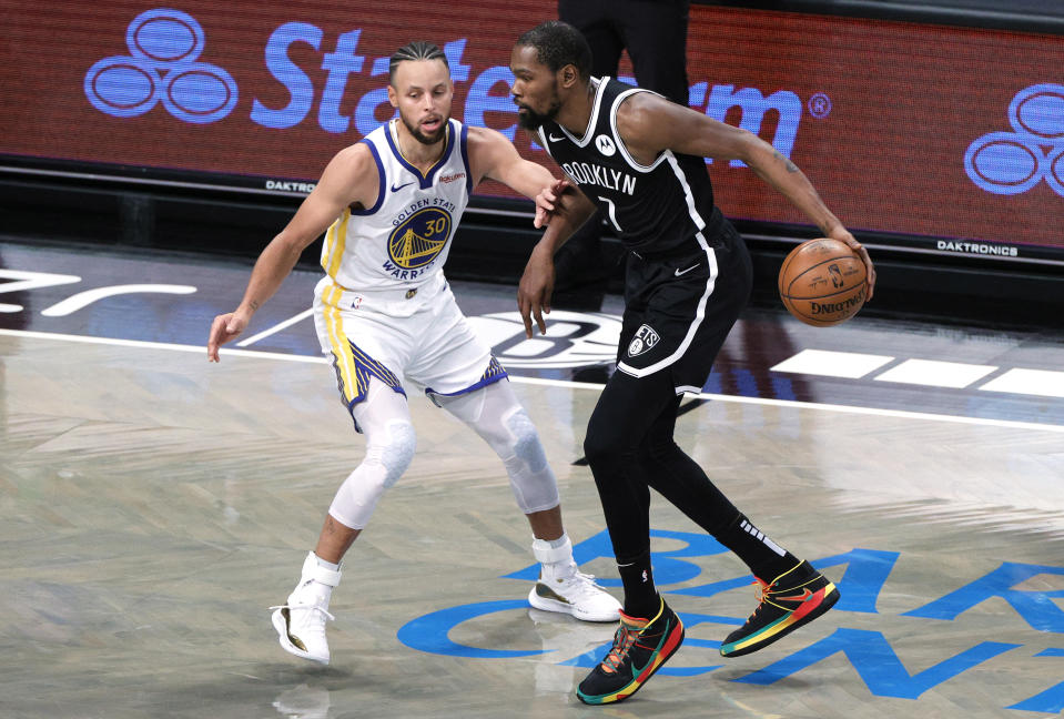 Kevin Durant dribbles against Stephen Curry.