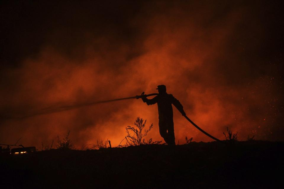 A firefighter battles with fire in Kirli village near the town of Manavgat, in Antalya province, Turkey early Friday July 30, 2021. The fire that continued all night could not be brought under control and people living in the village started to evacuate. Wildfires are common in Turkey's Mediterranean and Aegean regions during the arid summer months, although some previous forest fires have been blamed on arson.(AP Photo)