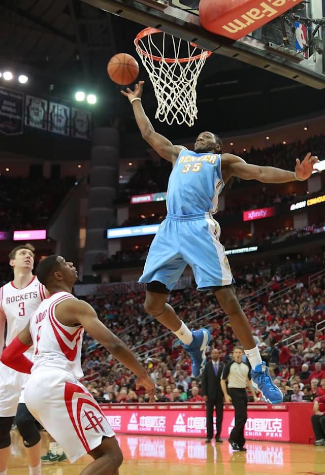 Denver Nuggets forward Kenneth Faried prepares to score on a pass above the rim as Houston Rockets center Omer Asik (3) and forward Terrence Jones watch during the first half of an NBA basketball game in Houston on Sunday, April 6, 2014. (AP Photo/Richard Carson)
