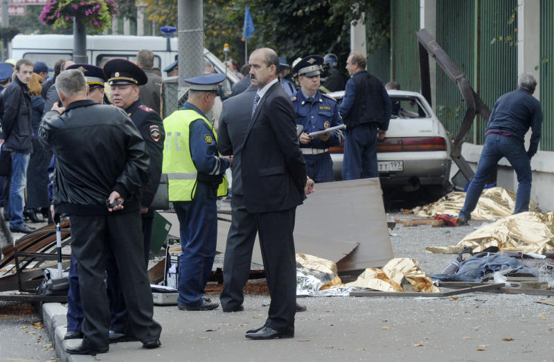 In this photo made Saturday, Sept. 22, 2012, law enforcement authorities work at the site of the crash where a heavily drunk driver killed seven people at a bus stop in Moscow, Russia.  Five orphaned teens were waiting for a bus with their guardians in Moscow on Saturday when a car careened into them, killing all seven. Grief turned to outrage when it emerged that the driver was heavily drunk and had a string of traffic violations on his record, and lawmakers have reacted with proposals to stiffen penalties on drunken drivers. (AP Photo)