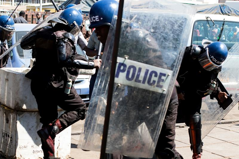<strong>Police surround an activist lying on the ground at Harare Central Police Station during a protest in August, 2016 amid anti-government marches in Zimbabwe</strong> (JEKESAI NJIKIZANA via Getty Images)