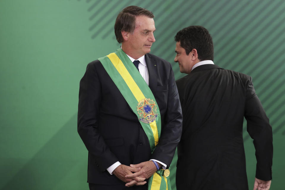 Brazil's new President Jair Bolsonaro, left, looks at his Justice Minister Sergio Moro, during a ministerial inauguration ceremony, at the Planalto Presidential palace, in Brasilia, Brazil, Tuesday, Jan. 1, 2019. (AP Photo/Eraldo Peres)