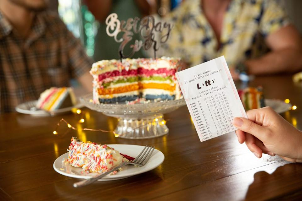 A woman holds a lotto ticket in front of a rainbow birthday cake.