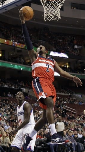 Washington Wizards' John Wall (2) goes up for a shot as Philadelphia 76ers' Jrue Holiday (11) looks on in the first half of an NBA basketball game, Friday, Jan. 13, 2012, in Philadelphia. (AP Photo/Matt Slocum)