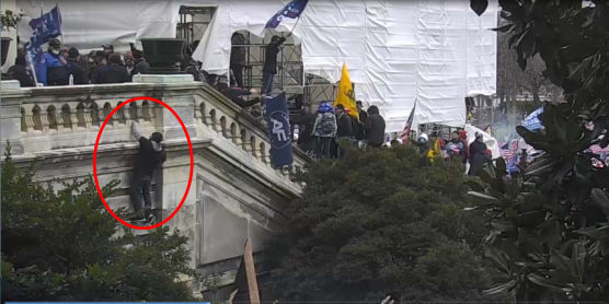 A surveillance image taken from the U.S. Capitol shows a man, whom prosecutors say is Iowan Doug Jensen, scaling the outside of the building during the Jan. 6 riot. Jensen is asking a D.C. judge to release him from custody while he negotiates a plea agreement with prosecutors.