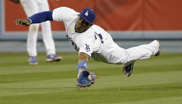 Los Angeles Dodgers right fielder Yasiel Puig fields a base hit by Arizona Diamondbacks' Paul Goldschmidt during the 12th inning of a baseball game in Los Angeles, Friday, April 18, 2014. (AP Photo/Chris Carlson)