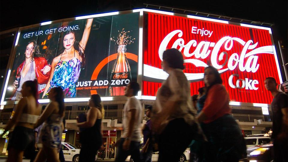 Sydney, Australia - March 22, 2014: A large group of people walk past two large neon Coca-Cola billboards on Kings Cross at night.