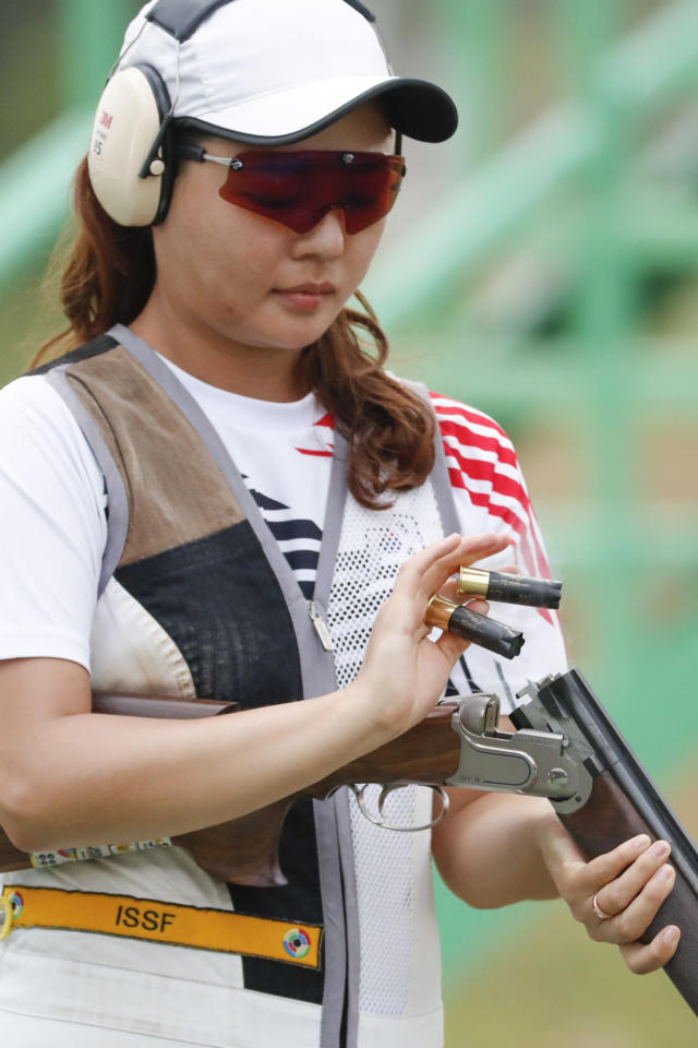 South Korea's Kim Minji ejects empty cartridges during the shooting skeet women's final at the 18th Asian Games in Palembang, Indonesia, Sunday, Aug. 26, 2018. (AP Photo/Vincent Thian)