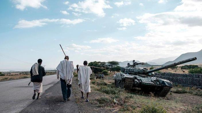 People walk next to an abandoned tank belonging to Tigray forces south of the town of Mehoni, Ethiopia - 11 December 2020