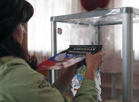 A member of a local electoral commission attaches a sticker with symbols of the self-proclaimed Donetsk People's Republic, replacing the coat of arms of Ukraine, onto a ballot box during the preparations for the upcoming election at a polling station in Donetsk, eastern Ukraine, October 31, 2014. REUTERS/Maxim Zmeyev