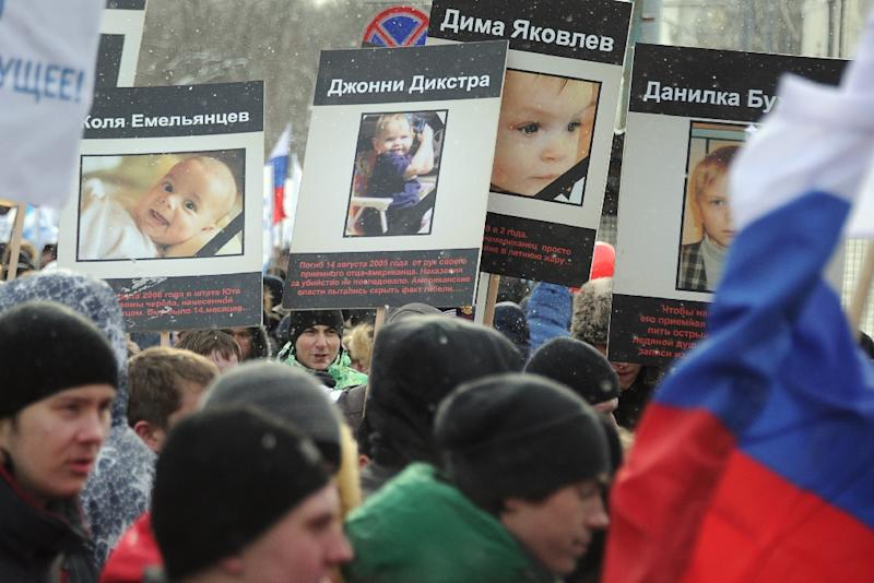 Pro-Kremlin children's advocacy groups march through Moscow on March 2, 2013, carrying the portraits of the Russian children who died in USA after being adopted there