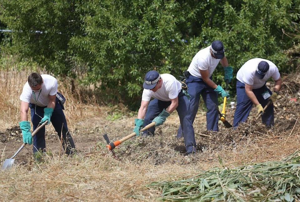 British police officers in 2014 clearing an area of wasteland during the search for evidence in the town of Praia da Luz (Picture: PA)