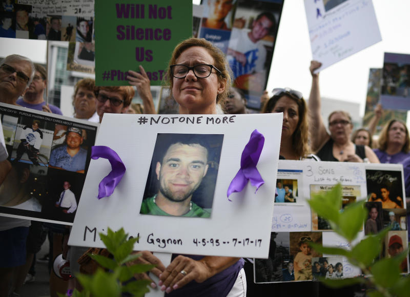 FILE - In this Friday, Aug. 17, 2018 file photo, Christine Gagnon of Southington, Conn. protests with other family and friends who have lost loved ones to OxyContin and opioid overdoses at Purdue Pharma LLP headquarters in Stamford, Conn. Gagnon lost her son Michael 13 months earlier. (AP Photo/Jessica Hill)