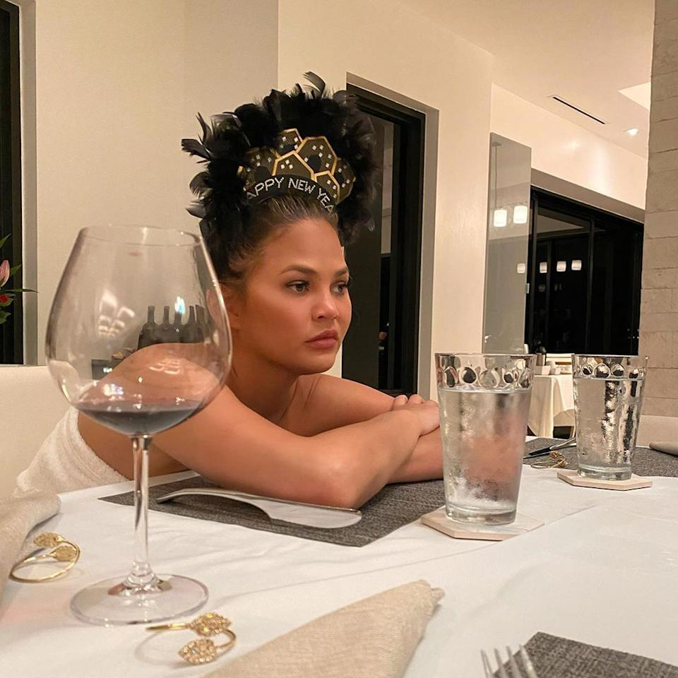 Chrissy Teigen seated at a table