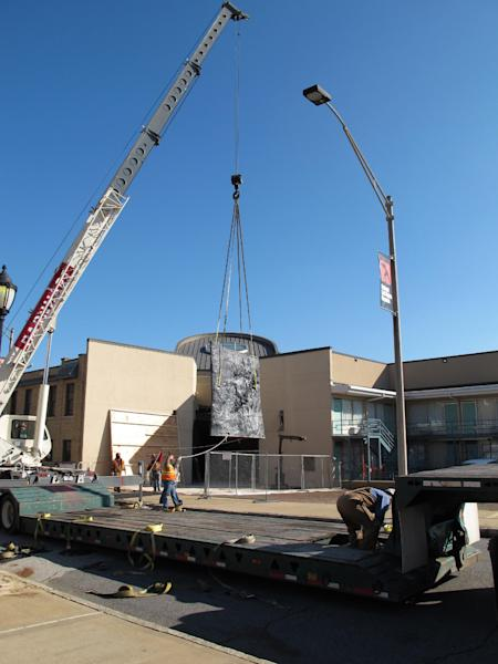A crane moves a piece of a 7-ton sculpture from the lobby of the National Civil Rights Museum onto a flatbed truck on Tuesday, Dec. 11, 2012 in Memphis Tenn. The sculpture was moved from the museum to make room for crews doing renovation work, which is expected to be completed in early 2014. The museum is located at the site of the old Lorraine Motel, which is where Martin Luther King Jr. was assassinated in 1968 in Memphis. (AP Photo/Adrian Sainz)
