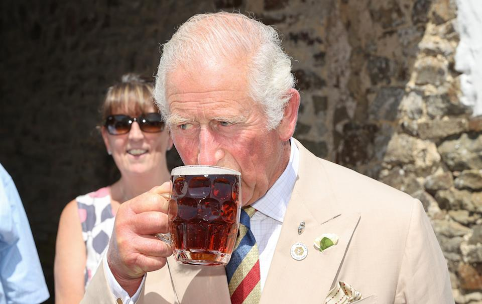 IDDESLEIGH, ENGLAND - JULY 21: Prince Charles, Prince of Wales drinks a pint of ale as he visits the Duke of York Inn to join author Sir Michael Morpurgo at a lunch club for local residents, with Camilla, Duchess of Cornwall during Day 3 of their visit to Devon and Cornwall on July 21, 2021 in Iddesleigh, England.  (Photo by Chris Jackson/Getty Images)