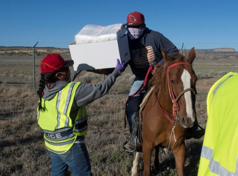 Native Americans of the Navajo Nation people pick up supplies on horses at a food bank set up at the Navajo Nation town of Casamero Lake The Navajo Nation now has the highest per capita COVID-19 infection rate in the country after surpassing New York. (AFP Photo/Mark RALSTON)