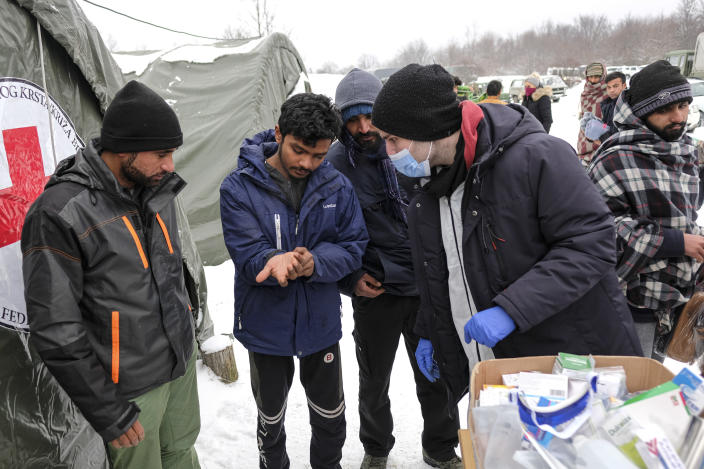 Medical staff examine migrants at the Lipa camp, outside Bihac, Bosnia, Monday, Jan. 11, 2021. Aid workers say migrants staying at a camp in northwestern Bosnia have complained or respiratory and skin diseases after spending days in make-shift tents and containers amid freezing weather and snow blizzards. Most of the hundreds of migrants at the Lipa facility near Bosnia's border with Croatia on Monday have been accommodated in heated military tents following days of uncertainty after a fire gutted most of the camp on Dec. 23. (AP Photo/Kemal Softic)