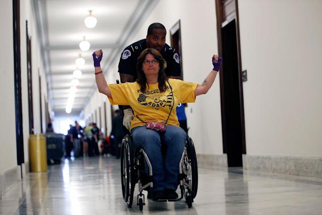 <p>A protestor is removed from a sit-in outside of Senate Majority Leader Mitch McConnell's office where they protested proposed cuts to Medicaid, Thursday, June 22, 2017 on Capitol Hill in Washington. (Photo: Jacquelyn Martin/AP) </p>