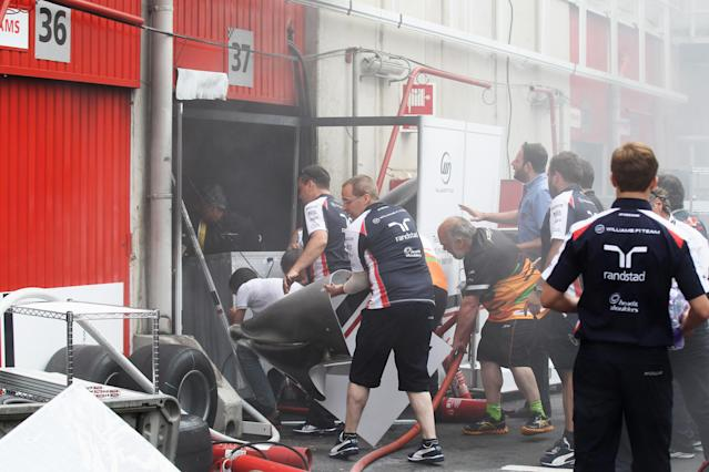 BARCELONA, SPAIN - MAY 13: Williams mechanics help fight the fire that broke out at the back of their team garage after they celebrated winning the Spanish Formula One Grand Prix at the Circuit de Catalunya on May 13, 2012 in Barcelona, Spain. (Photo by Mark Thompson/Getty Images)