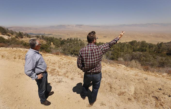 Tejon Ranch director of planning Nathan Keith, right, and Greg Medeiros, stand on a bluff overlooking the development