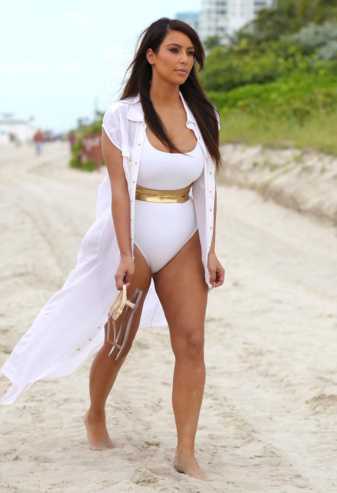Kim Kardashian in a white one piece swimsuit with a gold band around her waist at the beach in Miami Beach, FL. Kim was filming a segment for her new reality TV show alongside her sister Kourtney, who wore a plain white t-shirt with striped shorts and sandals. 