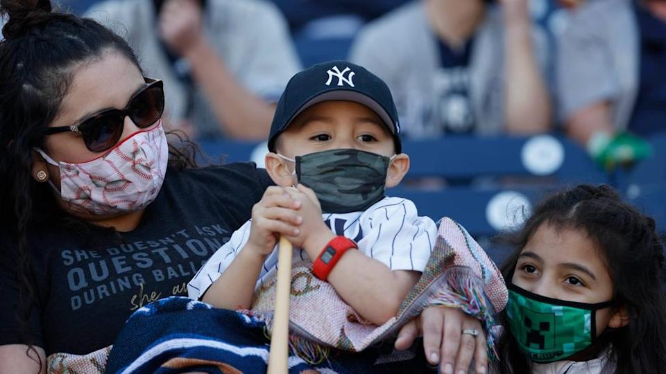 Yankees fans wearing masks in stands, three fans with little boy in middle