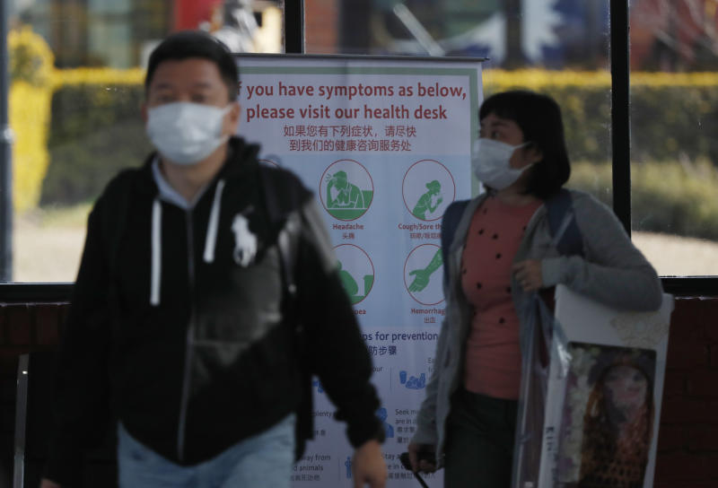 Passengers wearing face masks arrive at Tribhuwan International airport in Kathmandu, Nepal, Tuesday, Jan. 28, 2020. Authorities have started screening passengers after one confirmed case of a new coronavirus infection was detected in the Himalayan country. (AP Photo/Niranjan Shrestha)