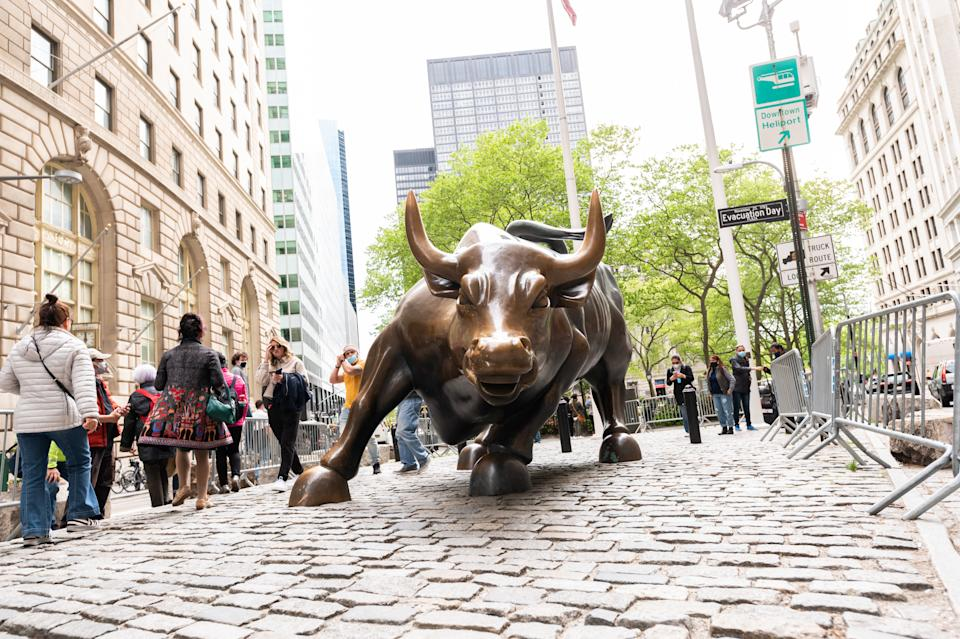 NEW YORK, NEW YORK - MAY 11: People visit the Charging Bull statue in Wall Street on May 11, 2021 in New York City. New York Governor Andrew Cuomo announced pandemic restrictions to be lifted on May 19.  (Photo by Noam Galai/Getty Images)