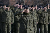 Members of Kosovo's Security Forces salute during the flag raising ceremony in this southeastern town of Gjilan, Kosovo on Thursday, Dec. 13, 2018, a day before the parliament votes to transform them into a regular army. Kosovo lawmakers are set to transform the Kosovo Security Force into a regular army, a move that significantly heightened tension with neighboring Serbia which even left open a possibility of an armed intervention in its former province. (AP Photo/Visar Kryeziu)