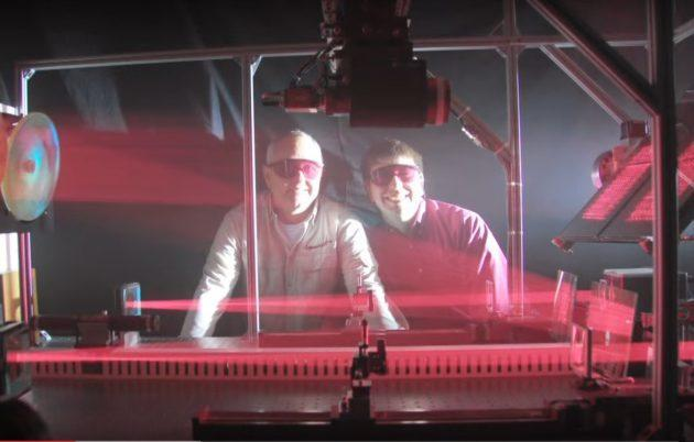LaserMotive's David Bashford and Tom Nugent monitor a laser experiment. (LaserMotive via YouTube)