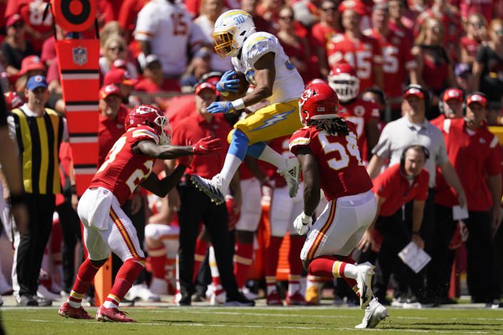 Los Angeles Chargers' Austin Ekeler (30) is tackled by Kansas City Chiefs' Rashad Fenton (27) and Nick Bolton (54) during the first half of an NFL football game, Sunday, Sept. 26, 2021, in Kansas City, Mo. (AP Photo/Charlie Riedel)