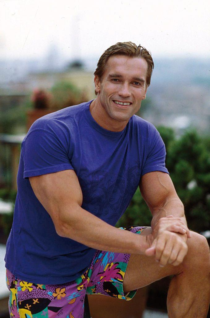 <p>Arnie showed off his Mr. Universe muscles in a tight t-shirt and bright tropical shorts. At this time, the Austrian-born bodybuilder had already transitioned into acting.</p>