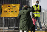People talk to staff at the entrance to a coronavirus testing facility in Sutton Coldfield, England, Tuesday Sept. 13, 2020. New measures are in place banning people from different homes from meeting together in some English cities, in response to a local rocketing coronavirus infection rate, although there is widespread criticism over the availability of testing facilities. (Jacob King/PA via AP)