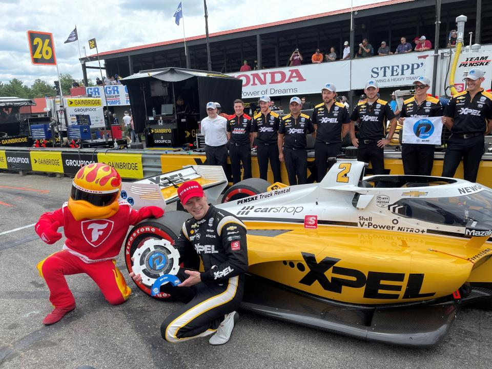 Josef Newgarden poses besides his Team Penske Chevrolet after winning the pole for the IndyCar race at Mid-Ohio Sports Car Course Saturday, July 3, 2021 in Lexington, Ohio. Newgarden will start alongside Colton Herta for Sunday's race in an All-American driver front row.(AP Photo/Jenna Fryer)